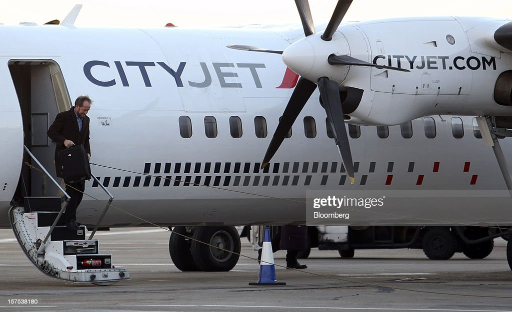 A passenger disembarks from a Fokker 50 aircraft, operated by CityJet Ltd., at City Airport in London, U.K., on Tuesday, Dec. 4, 2012. Air France-KLM Group's CityJet unit is studying options for a new investor, with a trade buyer a possibility given its strength at London City airport, Chief Executive Officer Christine Ourmieres said in an interview. Photographer: Chris Ratcliffe/Bloomberg via Getty Images