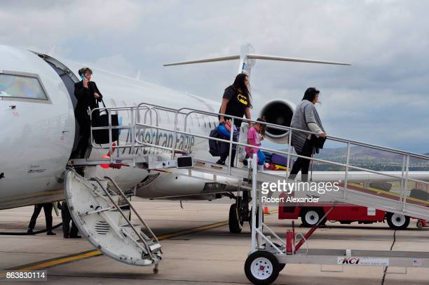 A passenger disembarks from an American Eagle passenger jet after landing at Santa Fe Municipal Airport in Santa Fe New Mexico