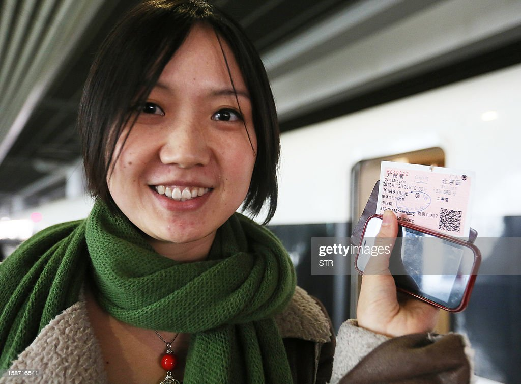 A passenger displays her ticket before boarding the new 2,298-kilometre (1,425-mile) line between Beijing and Guangzhou in Guangzhou, south China's Guangdong province on December 26, 2012. China launched service December 26 on the world's longest high-speed rail route, the latest milestone in the country's rapid and -- sometimes troubled -- super fast rail network. CHINA