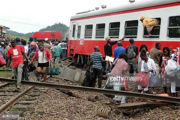 TOPSHOT A passenger escapes a train car using a window as others leave from the site of a train derailment in Eseka on October 21 2016 Fiftythree...