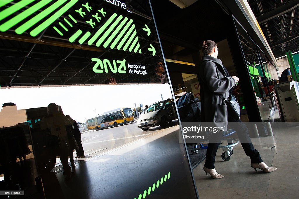 A passenger exits the departures terminal at Lisbon International (Portela) airport, operated by ANA-Aeroportos de Portugal SA, in Lisbon, Portugal, on Tuesday, Jan. 8, 2013. Portugal's government agreed to sell state-owned airport operator ANA-Aeroportos de Portugal SA to Vinci SA for 3.08 billion euros ($4.07 billion), raising money for the debt-strapped country. Photographer: Mario Proenca/Bloomberg via Getty Images
