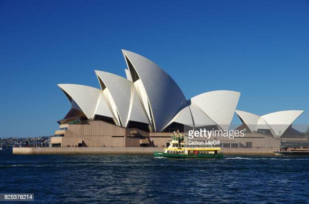 A passenger ferry passes the Sydney Opera House, Bennelong Point, Sydney, New South Wales, Australia