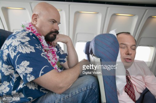 Passenger Frustrated by the Lack of Seating Space on a Aeroplane