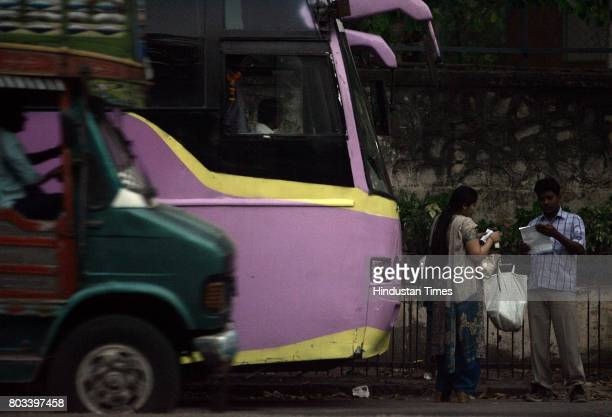 A passenger gets her ticket checked by a luxury bus conductor near Wadala Char Rasta