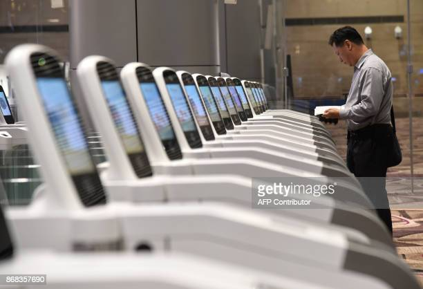 A passenger goes through an automated immigration gate at the newlyopened Changi International Airport's Terminal 4 in Singapore on October 31 2017...