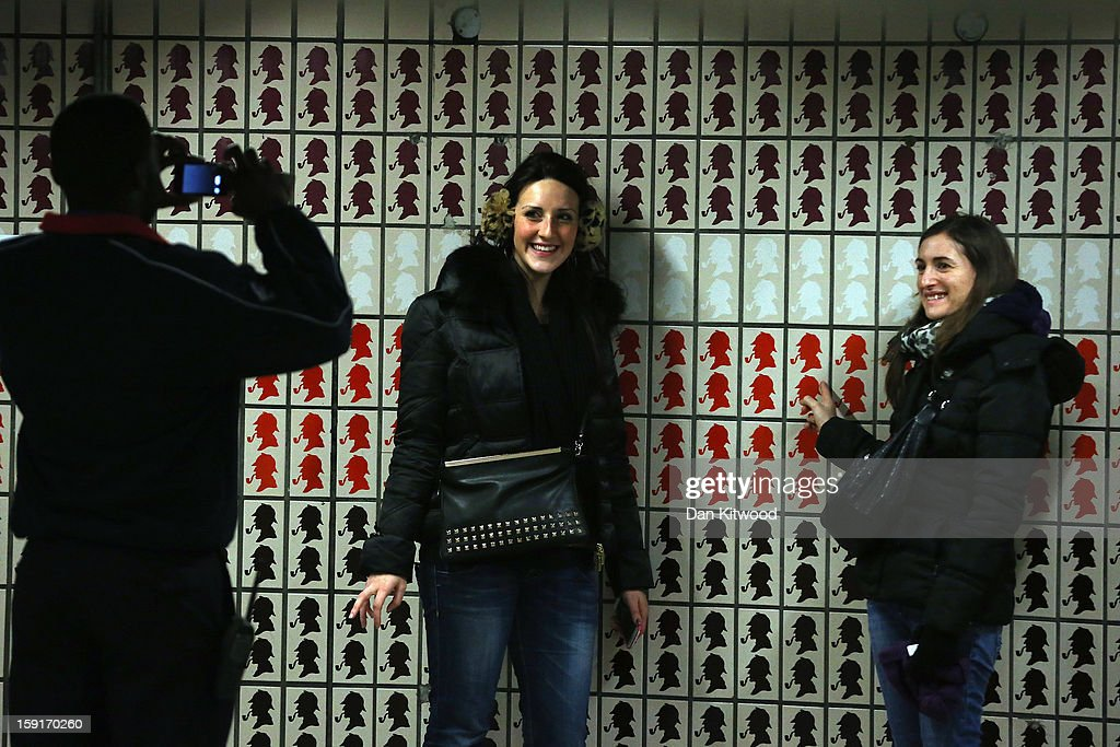 Passenger have their pictures taken in front of Sherlock Holmes themed tiles at Baker Street Underground Station on January 9, 2013 in London, England. Baker Street Station shares the 150th Anniversary of its opening on January 10th, 2013 with the London Underground. Commonly called the Tube, the London Underground is the oldest of its kind in the world and now carries approximately a quarter of a million people around its network of 249 miles of track every day. Baker Street station was remodeled between 1911-13 by architect Charles W Clark to its present form as part of a comprehensive rebuilding project by the Metropolitan Railways with the station as its new company headquarters and flagship station, where it quickly became known as the 'Gateway to Metro - Land'. Outside the Marylebone Road exit, a large statue commemorates Sherlock Holmes, Sir Arthur Conan Doyles ficticious detective who resided in the novels at 221B Baker Street.
