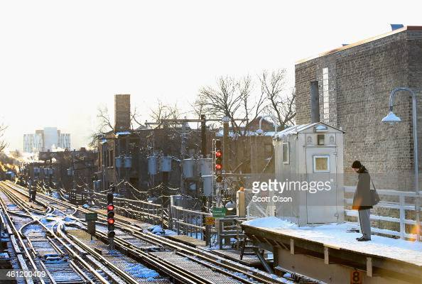 A passenger heading toward downtown waits on an 'L' platform for the train to arrive in below zero temperatures on January 7 2014 in Chicago Illinois...