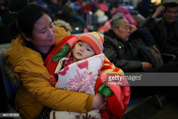 A passenger holds her baby in the waiting room of a railway station on January 21 2014 in Qingdao China The Chinese Spring Festival travel rush began...