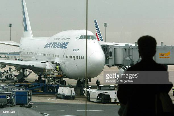 A passenger in silhouette watches an Air France aircraft at Roissy Charles de Gaulle airport September 25 2002 in Roissy France French airline pilots...