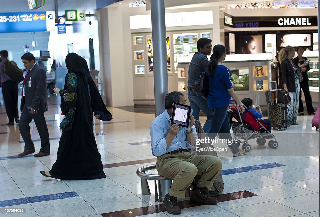 DUBAI, AIRPORT, United Arab Emirates - DECEMBER 25: A passenger is doing a telephone call with his Apple ipad with skype at Dubai Airport on December 25, 2011 in Dubai, United Arab Emirates
