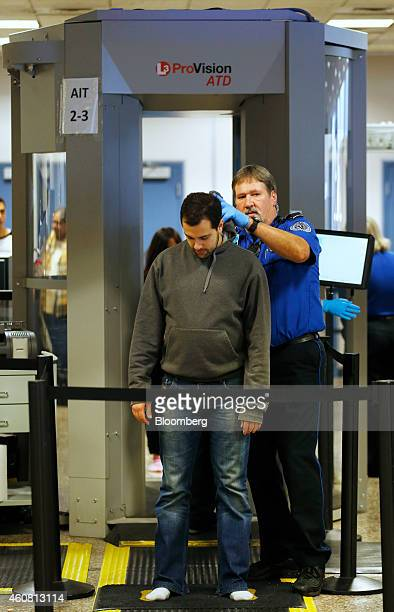 A passenger is searched by a Transportation Security Administration officer after passing through a body scanner at a security check point at Salt...