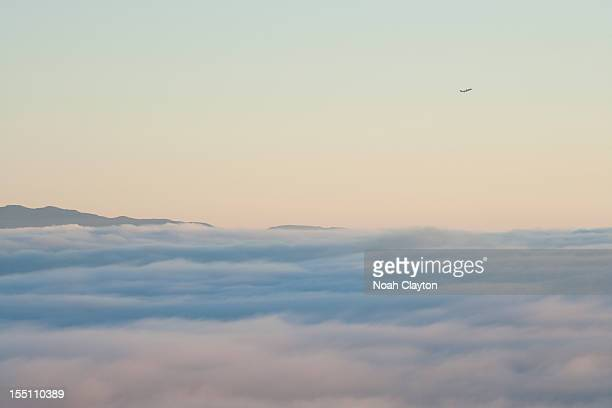 Passenger jet climbs above clouds and mountains