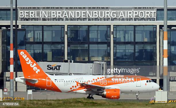 A passenger jet of airline easyJet taxis past the new and unfinished BER Willy Brandt Berlin Brandenburg International Airport on July 3 2015 in...