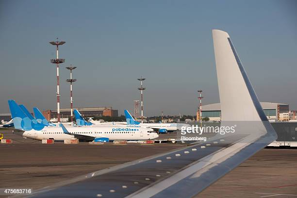 Passenger jets operated by Pobeda Airlines a lowcost unit of Aeroflot Russian Airlines OJSC stand on the tarmac beyond a winglet at Vnukovo...