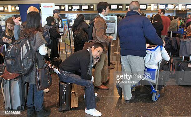 Passenger Koji Shinozaki seated at center uses his phone while waiting in line to check in to a Japan Airlines flight from Logan Airport A fire broke...