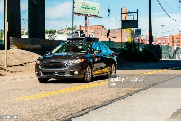 A passenger look on as he rides in a pilot model of an Uber selfdriving car on September 13 2016 in Pittsburgh Pennsylvania Uber launched a...