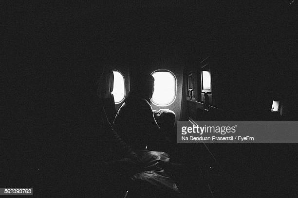 Passenger Looking Out Of Airplane Window