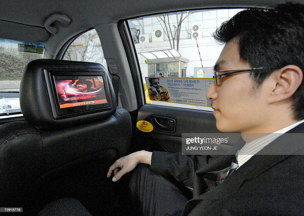 A passenger looks at a liquid crystal display screen situated in the back of the headrest on the front passenger seat in a taxi showing...