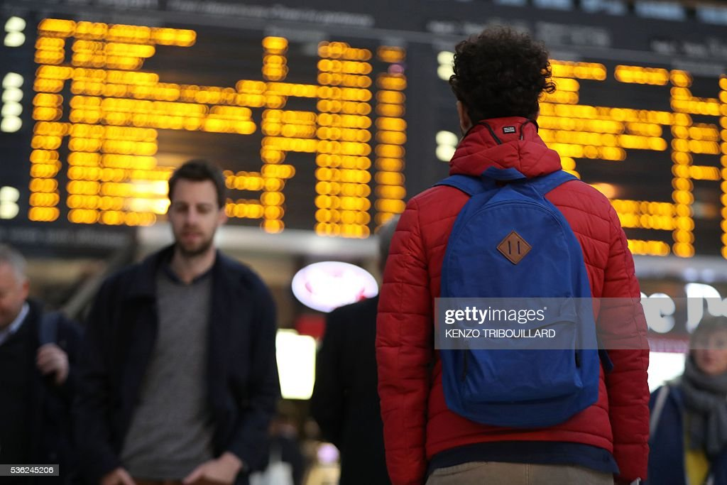 A passenger looks at the display panel indicating delayed trains on June 1, 2016 in Paris, at the Gare de Lyon railway station at the start of a strike by employees of French state-owned rail operator SNCF to protest against government labour reforms. Rail strikes in France are expected to take full effect, disrupting transport across the country just over a week before the Euro 2016 football championship starts. / AFP / KENZO