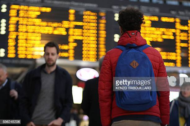 A passenger looks at the display panel indicating delayed trains on June 1 2016 in Paris at the Gare de Lyon railway station at the start of a strike...