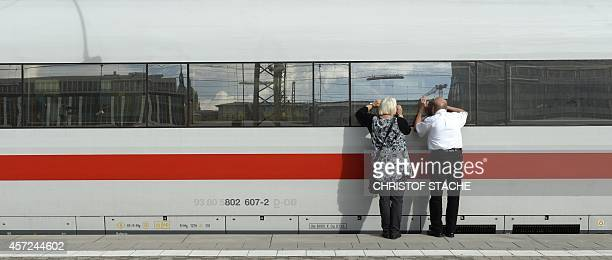 A passenger looks into a parked high speed train ICE of the German railway Deutsche Bahn at a platform of the central railway station in Munich...