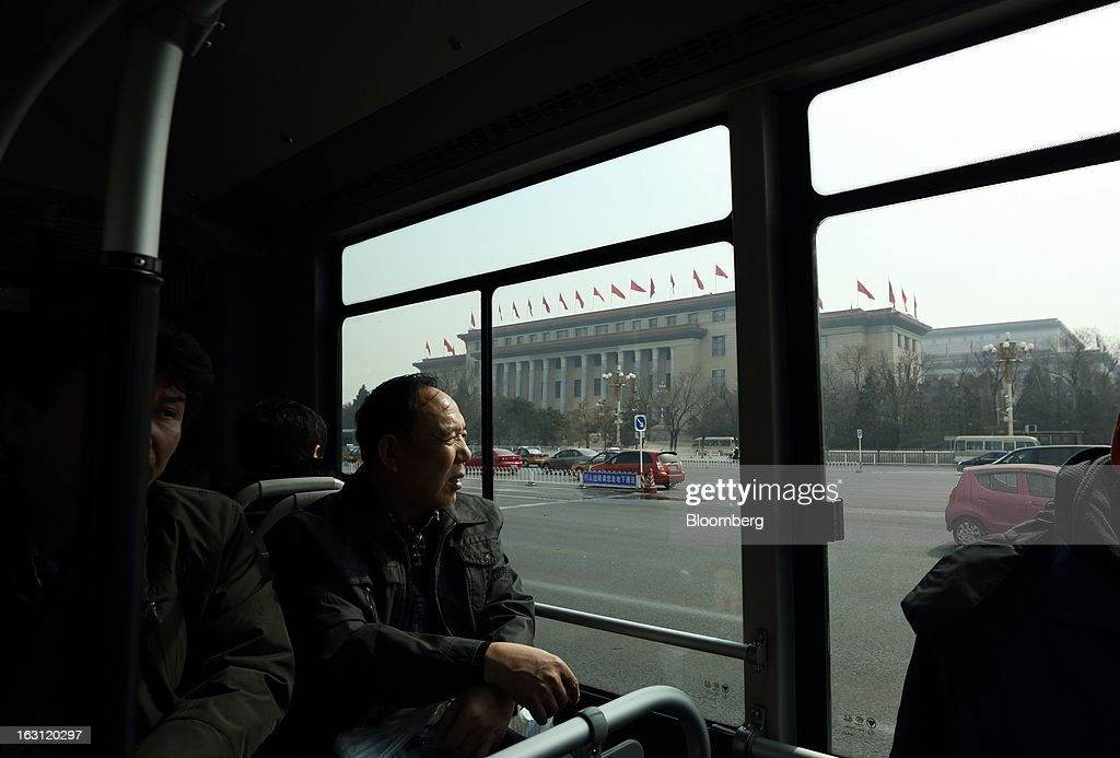 A passenger looks out of a bus window as it drives past the Great Hall of the People in Beijing, China, on Tuesday, March 5, 2013. China maintained its economic-growth target at 7.5 percent for 2013 while setting a lower inflation goal of 3.5 percent, setting up a challenge for new leaders to keep prices in check without harming expansion. Photographer: Tomohiro Ohsumi/Bloomberg via Getty Images