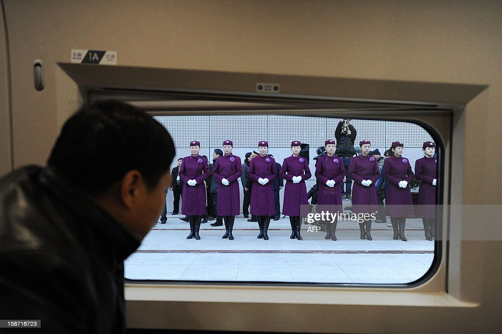A passenger looks out of the high speed train of the new 2,298-kilometre (1,425-mile) line between Beijing and Guangzhou as it waits to start off in Beijing on December 26, 2012. China started service on December 26 on the world's longest high-speed rail route, the latest milestone in the country's rapid and -- sometimes troubled -- super fast rail network. The opening of this new line means passengers will be whisked from the capital to the southern commercial hub in just eight hours, compared with the 22 hours previously required. CHINA OUT AFP PHOTO