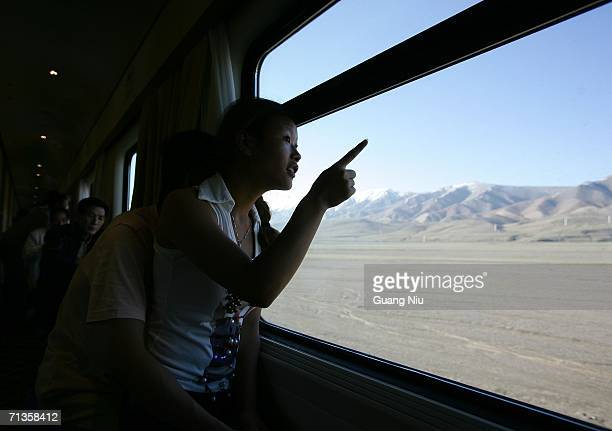 A passenger looks outside at the first train to travel from Beijing to the Tibetan capital Lhasa runs after it leaves Golmud station on July 3 2006...