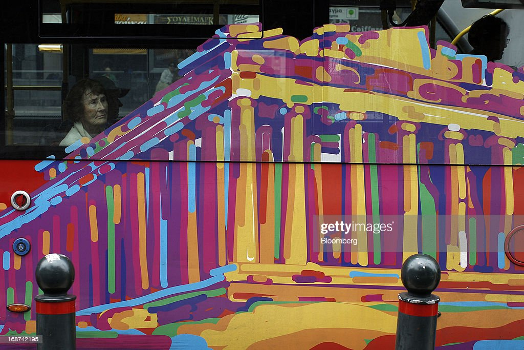 A passenger looks through the window of a public bus decorated with a Parthenon Temple design in Athens, Greece, on Tuesday, May 14, 2013. Greek Prime Minister Antonis Samaras said the country can beat the targets set under its 240 billion-euro ($311 billion) International Monetary Fund and euro area bailout program and return to bond markets in the first half of next year. Photographer: Kostas Tsironis/Bloomberg via Getty Images