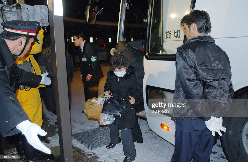 A passenger (C) of a derailed bullet train Komachi arrives at the Akita station by bus in Akita city, northern Japan on March 2, 2013, after a Japanese bullet train carrying about 130 passengers and crew derailed in heavy snow. There were no reports of injuries, the rail operator said.