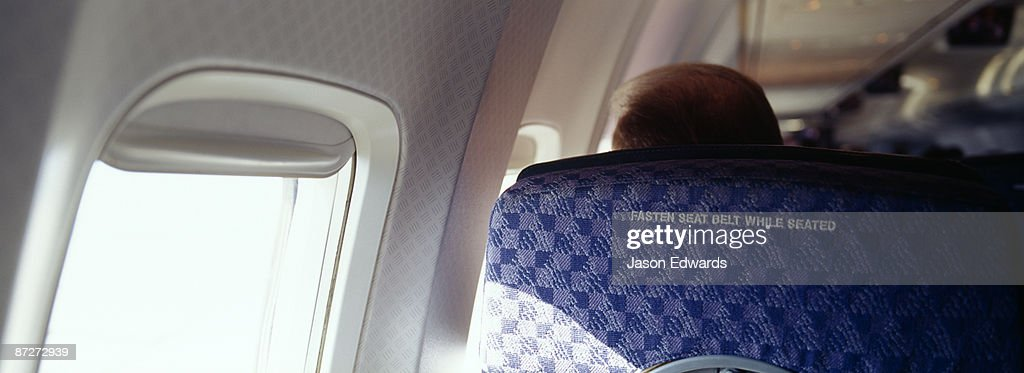 A passenger on a commercial aircraft and the fasten seat belts sign.
