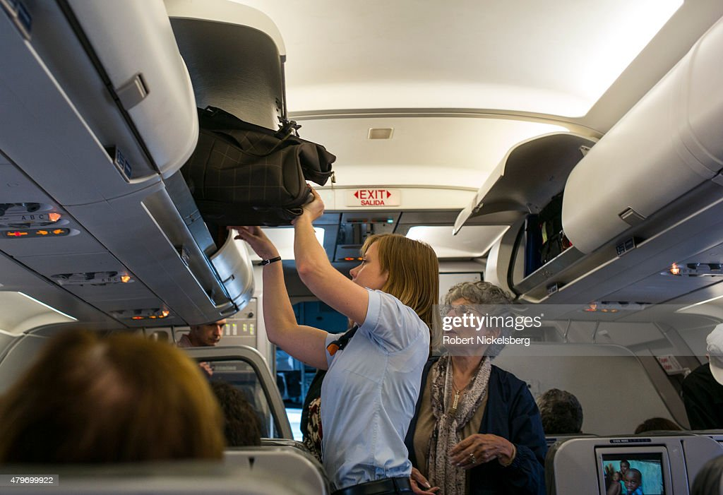 A passenger on a JetBlue Airways flight from New York's JFK International Airport center right receives help with her carryon luggage from an airline...