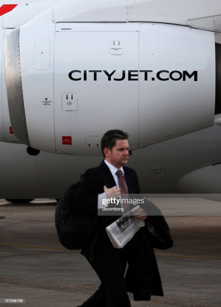 A passenger passes an Avro RJ85 aircraft, operated by CityJet Ltd., after landing at City Airport in London, U.K., on Tuesday, Dec. 4, 2012. Air France-KLM Group's CityJet unit is studying options for a new investor, with a trade buyer a possibility given its strength at London City airport, Chief Executive Officer Christine Ourmieres said in an interview. Photographer: Chris Ratcliffe/Bloomberg via Getty Images