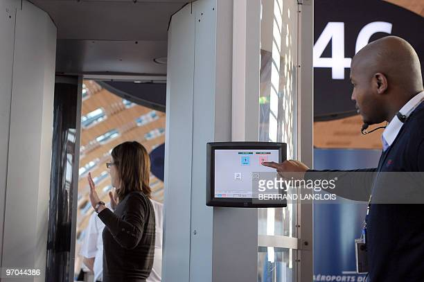 A passenger passes on February 22 through a new body scanner introduced today for experimentation at Paris' Charles de Gaulle international airport...
