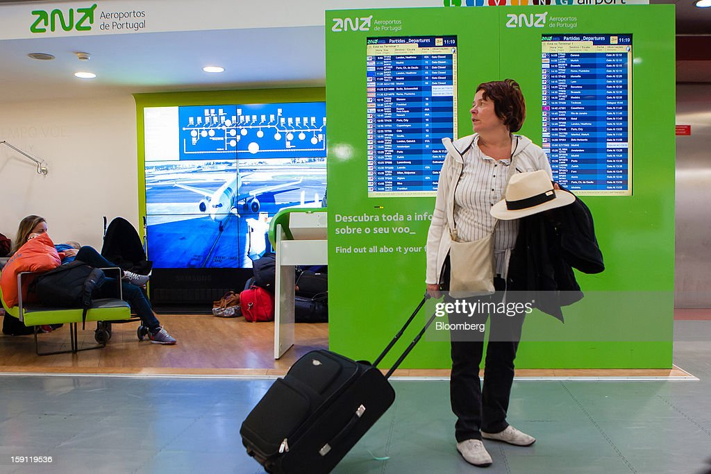 A passenger pauses with her luggage in front of flight information screens at Lisbon International (Portela) airport, operated by ANA-Aeroportos de Portugal SA, in Lisbon, Portugal, on Tuesday, Jan. 8, 2013. Portugal's government agreed to sell state-owned airport operator ANA-Aeroportos de Portugal SA to Vinci SA for 3.08 billion euros ($4.07 billion), raising money for the debt-strapped country. Photographer: Mario Proenca/Bloomberg via Getty Images