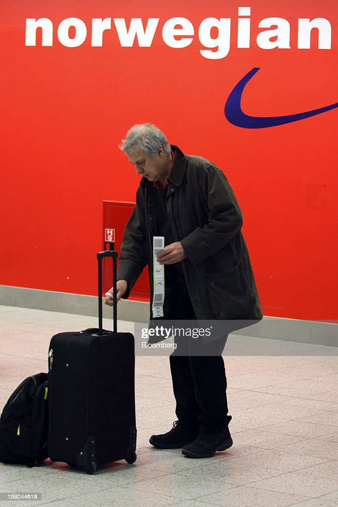 A passenger places an identification label on to their luggage at the Norwegian Air Shuttle AS self-service check-in area at Gatwick airport in Crawley, U.K., on Thursday, Jan. 10, 2013. Gatwick, acquired by Global Infrastructure Partners Ltd. in 2009 after regulators sought a breakup of BAA Ltd., owner of the larger Heathrow hub, is 30 miles (48 kilometers) south of London and serves about 200 destinations, more than any other U.K. airport, according to flight schedule data provider OAG. Photographer: Chris Ratcliffe/Bloomberg via Getty Images