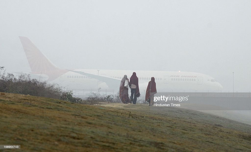 A passenger plane at the runway waits to take off as dense fog engulf the area around Delhi International Airport as Mercury dips further to below 3 degrees on Friday Morning on January 4, 2013 in New Delhi, India. Dense fog has affected around 45 trains and 22 flights.