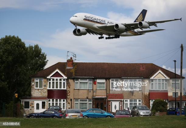 A passenger plane comes into land near housing at Heathrow Airport on August 11 2014 in London England Heathrow is the busiest airport in the United...