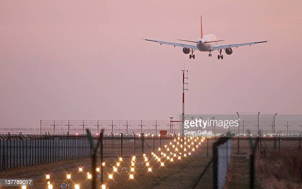A passenger plane lands at Schoenefeld Aiport near the construction site and the new control tower of the new Berlin Brandenburg International Aiport...