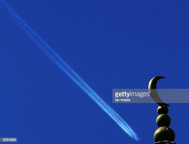 A passenger plane leaves a vapour trail behind the minaret of Finsbury Park Mosque as members of the extreme rightwing group the National Front hold...