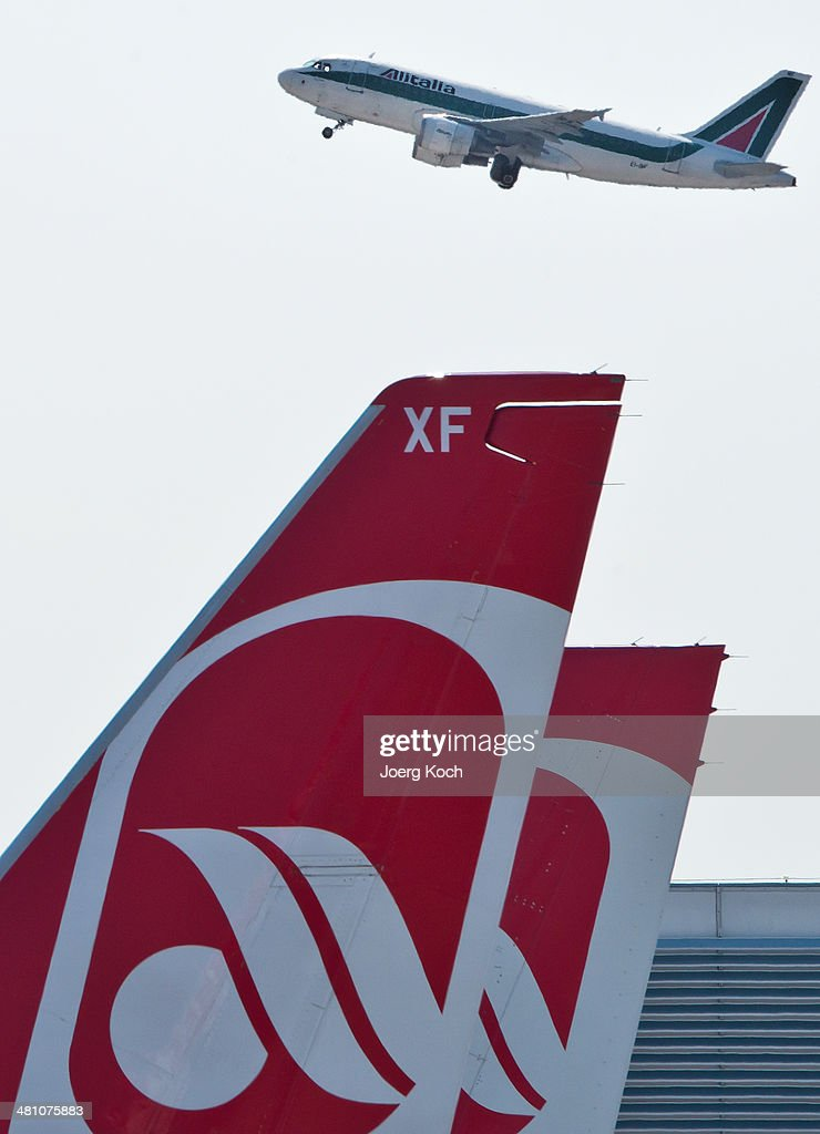 A passenger plane of Italian airline Alitalia starts past planes of German airline Air Berlin at Munich International Airport on March 28 2014 in...