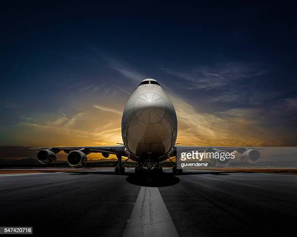 Passenger plane on runway at sunset