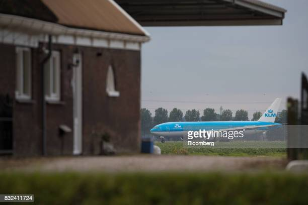 A KLM passenger plane operated by the Dutch arm of Air FranceKLM Group taxis beyond a farm building after landing at Schiphol airport in Amsterdam...
