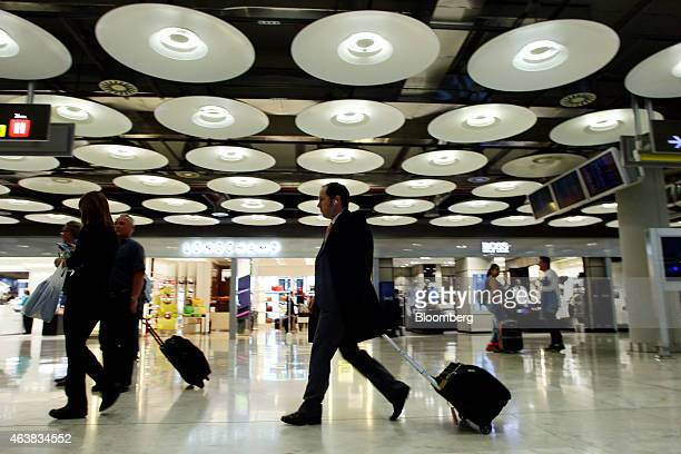 Passenger pull their luggage passed duty free stores inside Madrid Barajas airport operated by Aena SA in Madrid Spain on Wednesday Feb 18 2015 Aena...