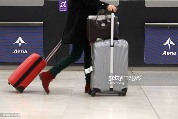 A passenger pulls their luggage passed Aena SA logos displayed in a terminal building inside Madrid Barajas airport in Madrid Spain on Wednesday Feb...