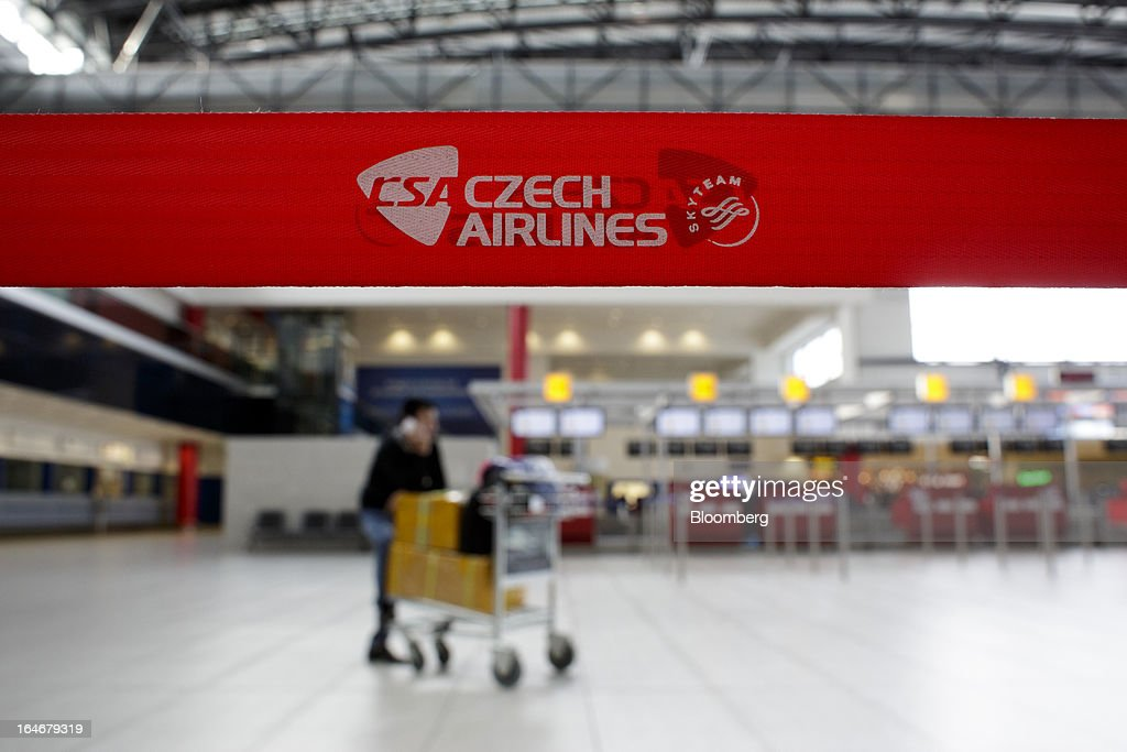 A passenger pushes a luggage trolley past a Ceske Aerolinie AS (CSA) airlines belt barrier at Vaclav Havel airport in Prague, Czech Republic, on Monday, March 25, 2013. Korean Air Lines Co. pledged to hold its stake in Ceske Aerolinie AS for five years, while CSA's majority owner will refrain from making 'significant' changes in its strategy, according to terms of this week's sale. Photographer: Martin Divisek/Bloomberg via Getty Images