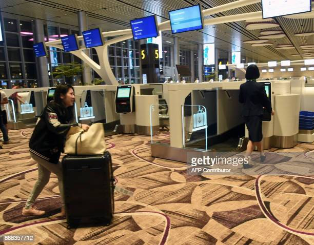 A passenger pushes her luggage towards an automated checkin booth at the newlyopened Changi International Airport's Terminal 4 in Singapore on...