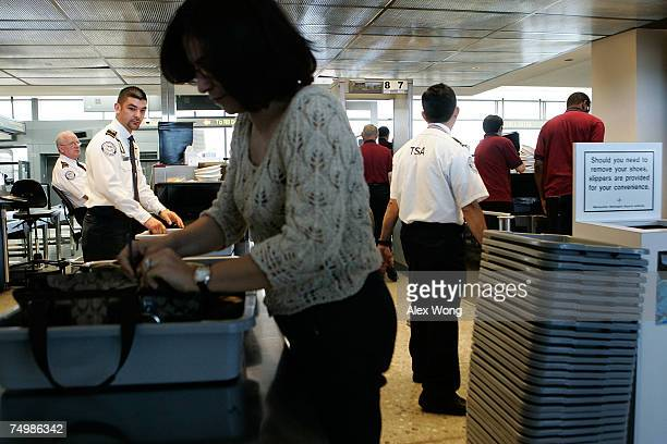 A passenger puts her carryon luggage in a tray for xray inspection before she passes through a security checkpoint at Dulles International Airport...