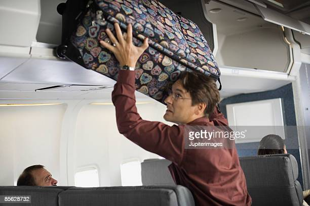 Passenger putting baggage in overhead compartment