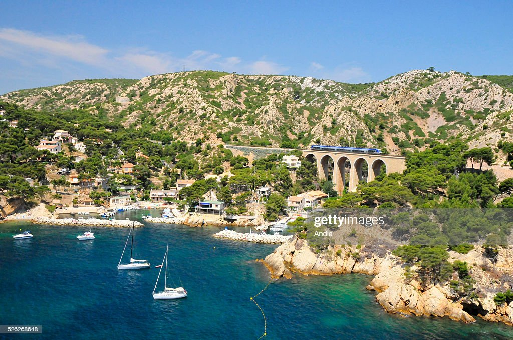 Passenger rail transport along the Mediterranean Sea Train on the viaduct small harbour of Mejean and sailboats lying at anchor